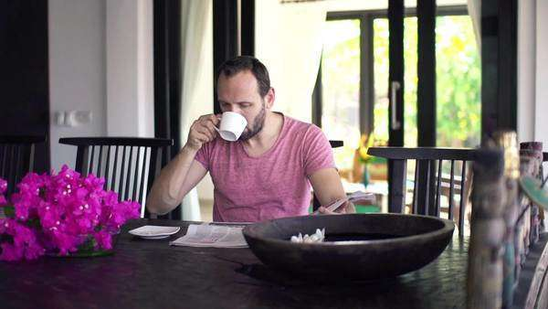 Young man reading newspaper and drinking coffee by dining table Royalty-free stock video