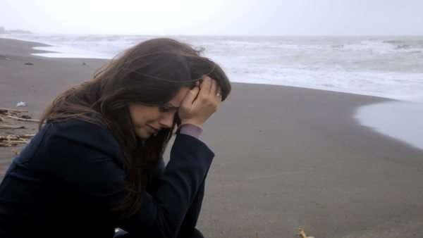A sad girl crying on the beach