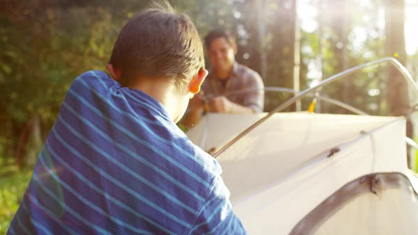 Happy American Caucasian father teaching son build tent in forest outdoors  stock footage