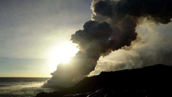Sunlight over Kilauea erupting volcano boiling magma flowing into the  Pacific ocean creating clouds of steam Big Island Hawaii USA stock footage