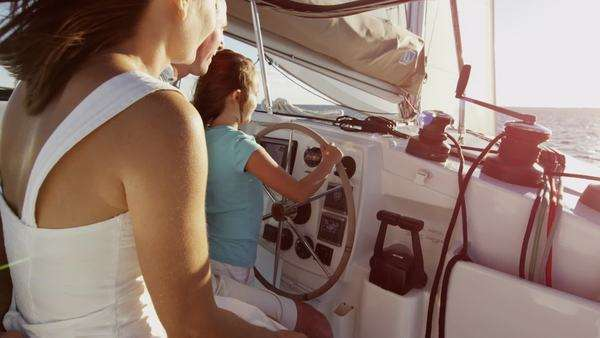 Husband and wife couple with young daughter having fun driving a yacht Royalty-free stock video