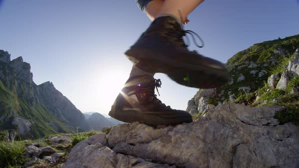 Slow Motion Close Up Lens Flare Young Woman Hiking Up The Mountain Slope Wearing Leather Mountaineering Boots Hiker Girl On Mountain Trekking