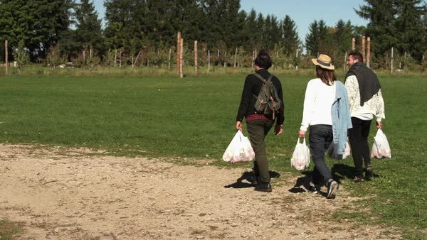 Wide shot of three people walking in orchard with plastic bags Royalty-free stock video