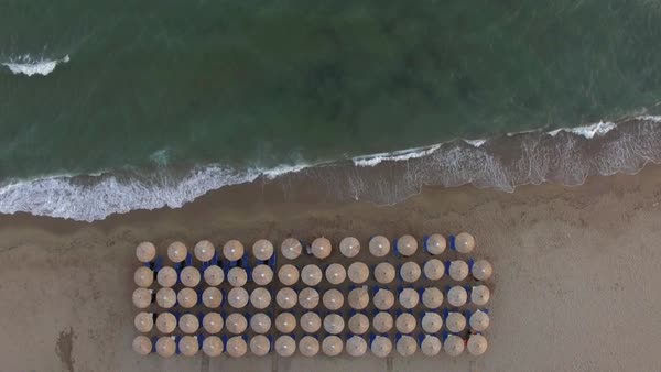 Aerial Sea And Shore With Rows Of Empty Sunbeds Under Straw Umbrellas Waves Rolling In On The Beach Stock Footage