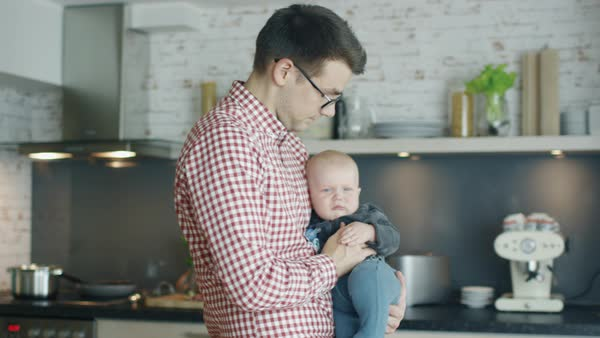 In the kitchen, a young father holds his baby Royalty-free stock video
