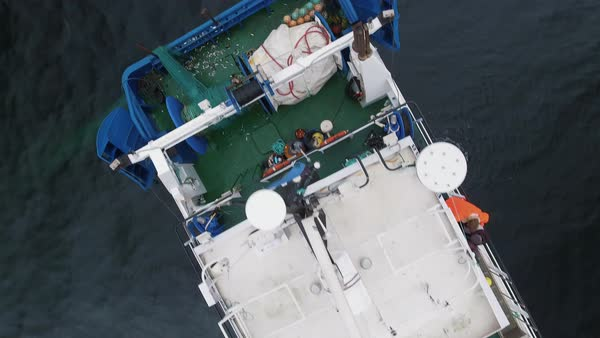 Flying over a commercial ship fishing with trawl net at the sea. Royalty-free stock video