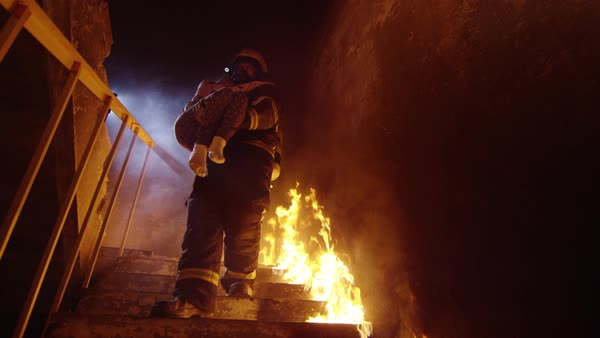 Fireman descends burning stairs with rescued little girl in his arms Royalty-free stock video