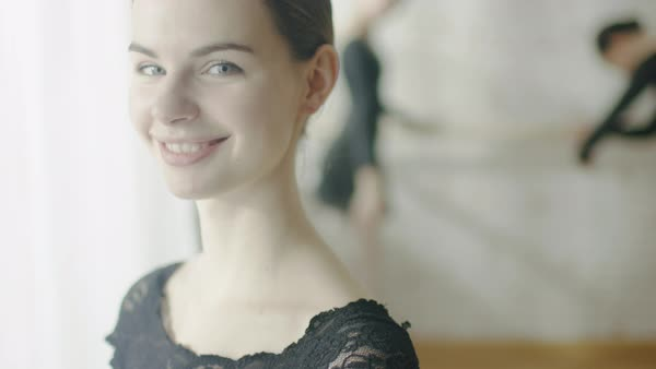Close-up portrait of a  young ballerina smiling and doing stretching at the barre Royalty-free stock video