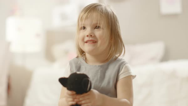 Happy little girl plays with plush toys in her room. Slow motion. Royalty-free stock video