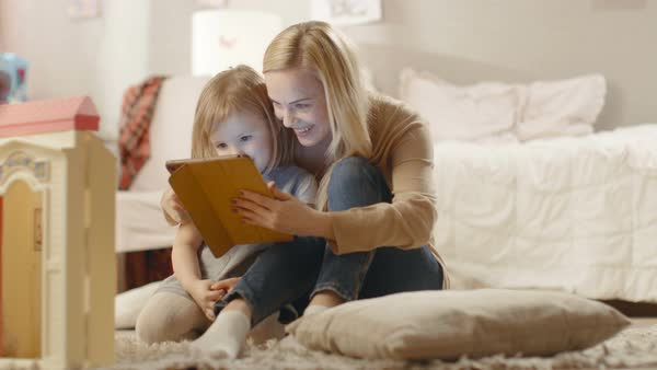 Beautiful mother and her little daughter sitting on the floor and reading children's books on a tablet computer. Slow motion. Royalty-free stock video