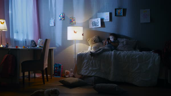 Cute little girl lies on her bed and watches cartoons on a smartphone. Her kitten is beside her playing. Her floor lamp is on. Royalty-free stock video