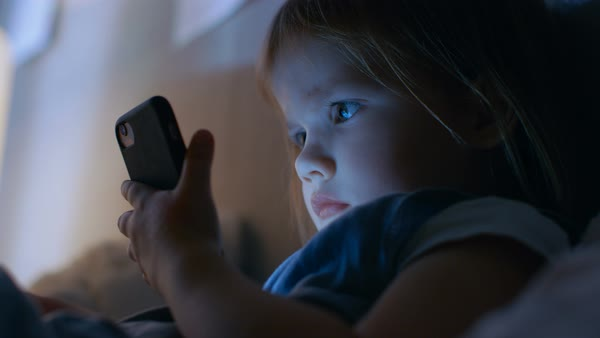 Cute little girl watches cartoons on a smartphone. Royalty-free stock video