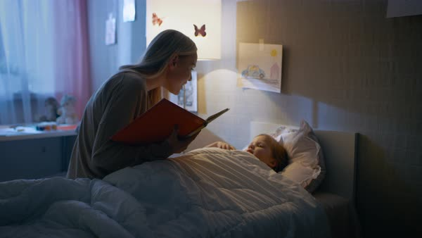 Young loving mother reads bedtime stories to her little beautiful daughter who goes to sleep in her bed. Royalty-free stock video