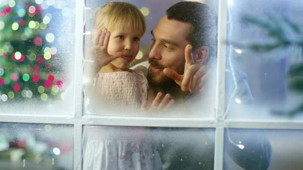 On Christmas Eve Father and His Cute Daughter Looks Through the Snowy, Frozen Window and Smile. Royalty-free stock video