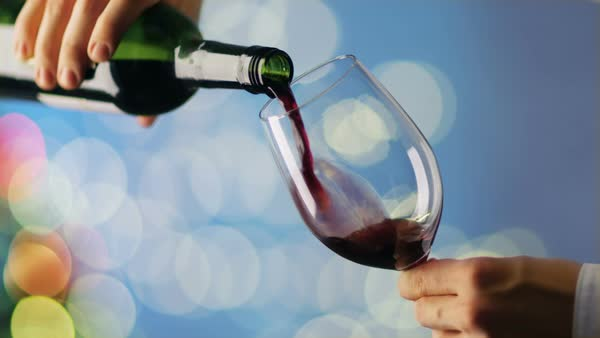 Man Wearing White Shirt Pouring Red Wine into Wine Glass. Background is Blue with Blurred Lights Shining. Royalty-free stock video