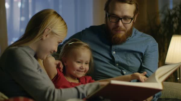 Father, mother and little daughter reading children's book on a sofa in the living room. It's evening. Royalty-free stock video