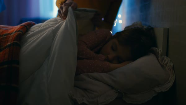 Sweet little girl sleeps in her bed at night, her mother tucks her blanket in. Royalty-free stock video