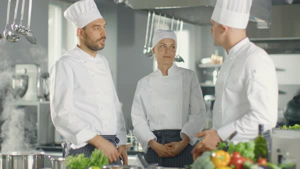 In the Modern Kitchen Team of Cooks Have Discussion. Kitchen is Full of Food Ingredients, Vegetables, Meat, Boiling Soup. Royalty-free stock video