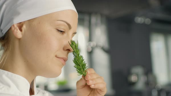 Beautiful Young Female Chef Smells Decorative Spice Plant. Royalty-free stock video