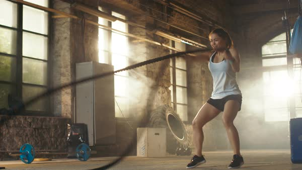 Athletic female actively in a gym exercises with battle ropes during her fitness workout high-intensity interval training Royalty-free stock video