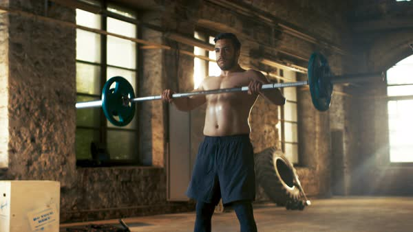 Strong athletic shirtless man lifts heavy barbell as a part of fitness training routine Royalty-free stock video