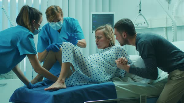 In the hospital, woman in labor pushes to give birth ...