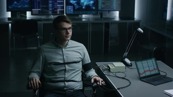 Young handsome suspect during interrogation undergoes lie detector /  polygraph test, connected to the machine he answers yes or no questions  which computer records and shows if he's lying stock