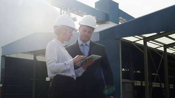 Managers in hard hats are talking and using tablet pc in industrial environment Royalty-free stock video