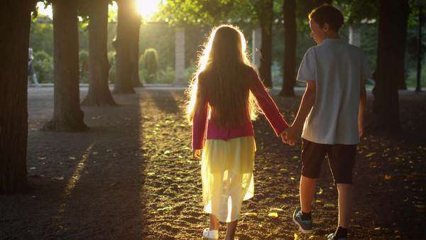 Boy and girl are holding hands together and walking at park Royalty-free stock video