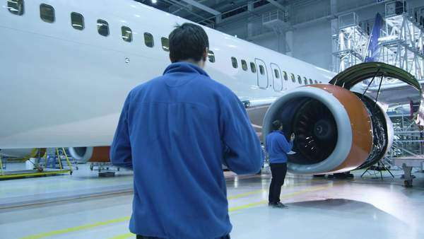 Aircraft maintenance mechanic in blue uniform is walking to greet his colleague who is checking the plane turbine blades in a hangar. Royalty-free stock video