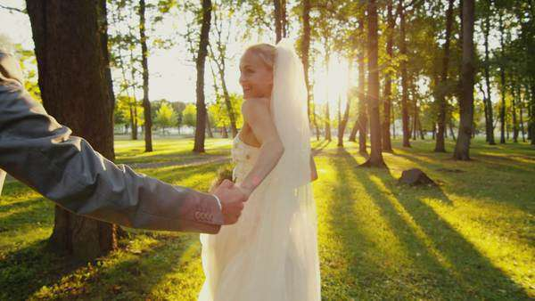 Smiling bride holds groom by the hand and runs in a park. Royalty-free stock video