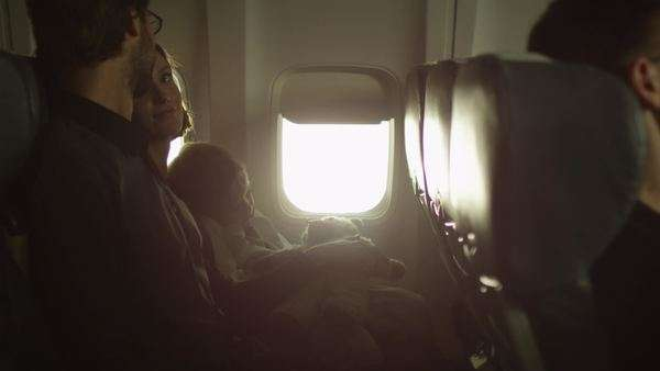 Young family with a boy sit inside an airplane next to a window. Royalty-free stock video