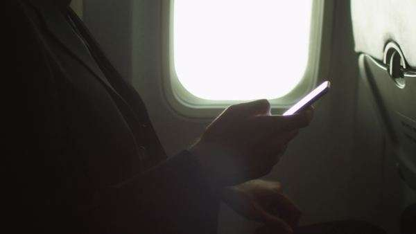 Young man in close-up is using a smartphone inside an airplane next to a window. Royalty-free stock video