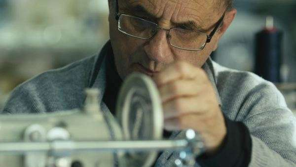 Old man in glasses is working on a sewing machine. Royalty-free stock video