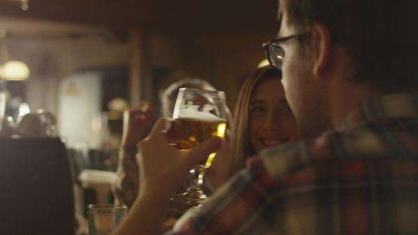Friends laugh, drink beer and cocktails while having a good time together at a bar. Royalty-free stock video