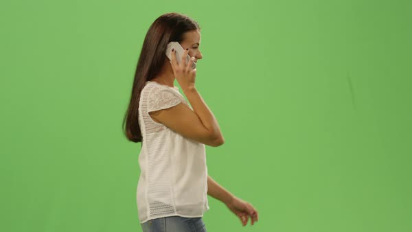 Casual young brunette girl is walking and talking on the phone on a mock-up green screen in the background. Royalty-free stock video