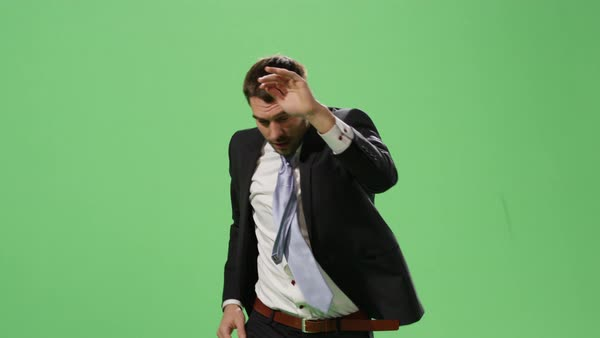 Serious businessman in a suit is running and spreading hands on a mock-up green screen in the background. Royalty-free stock video