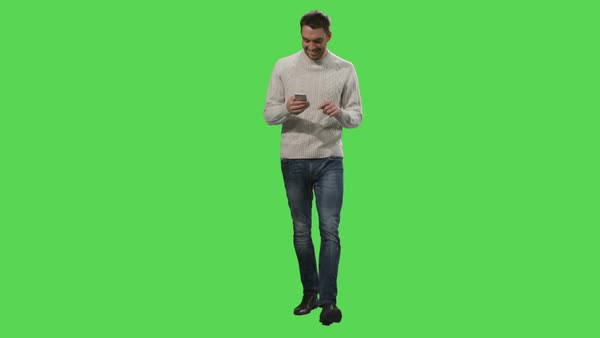 Casual caucasian man is walking and using smartphone on a mock-up green screen in the background. Royalty-free stock video
