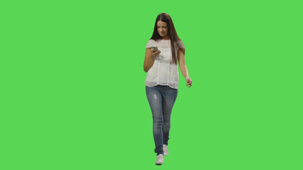 Casual brunette woman is walking and using a smartphone on a mock-up green screen in the background. Royalty-free stock video