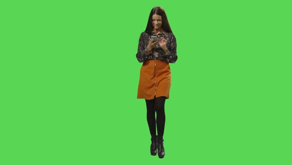 Casual brunette girl is walking and using a smartphone on a mock-up green screen in the background. Royalty-free stock video