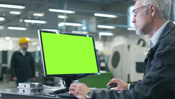 Senior engineer in glasses is working on a desktop computer with a green screen on monitor in a factory. Royalty-free stock video