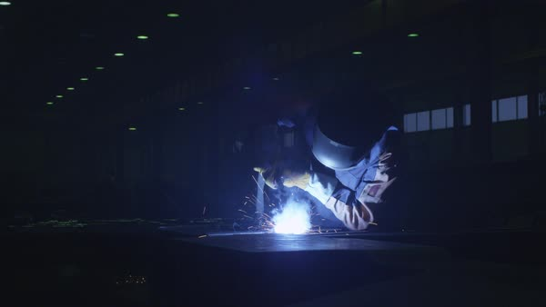 Heavy industry worker at a factory is welding metal in dark interior. Royalty-free stock video