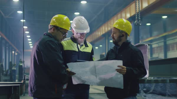 Team of workers at a heavy industry factory have a conversation while looking at a blueprint. Royalty-free stock video