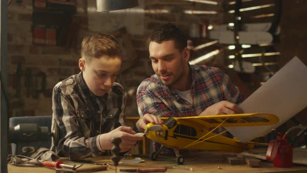 Father and son are modeling a toy airplane in a garage at home. Royalty-free stock video