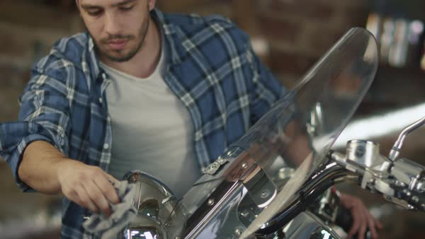 Man is cleaning and polishing chrome objects on his motorcycle in a garage. Royalty-free stock video