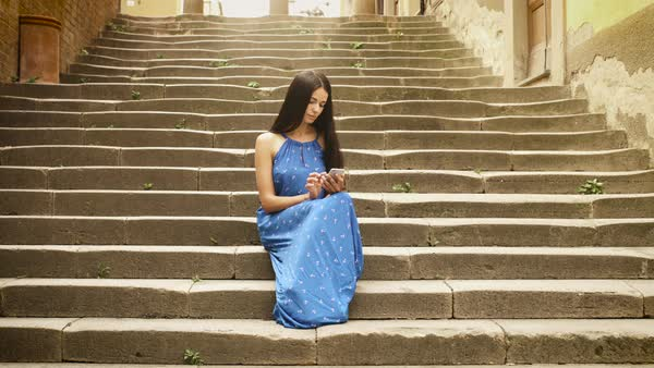 Attractive young brunette woman in light summer dress sitting on steps of stairs of European town. She is looking at her mobile phone and using it. Royalty-free stock video