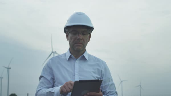 Senior engineer using tablet computer outdoors, wind turbines on background. Royalty-free stock video