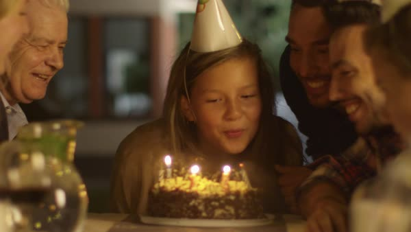 Happy Smiling Girl Blowing Candles out on her Birthday Cake. Girl Surrounded by Her Family and Friends Royalty-free stock video