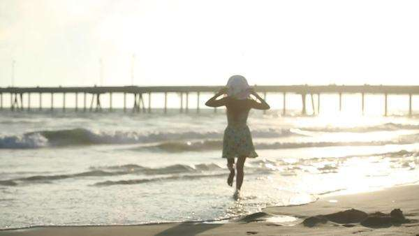 Handheld shot of woman running towards the ocean Royalty-free stock video