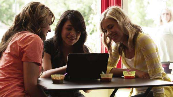 Medium shot tilt-up of Three young women using laptop in cafe, Provo, Utah Royalty-free stock video